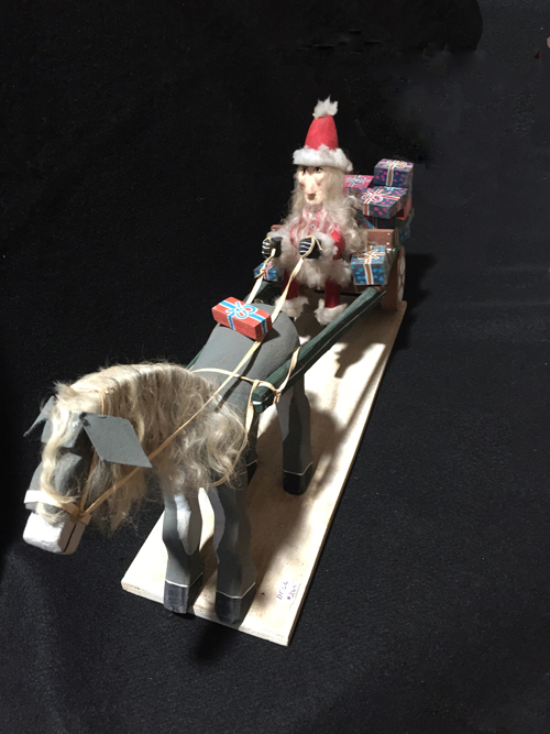Folk art Santa Claus delivers gifts by horse drawn cart